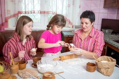 Mom teaching her two daughters cooking on the kitchen. Royalty Free Stock Images