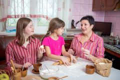 Mom teaching her two daughters cooking on the kitchen. Royalty Free Stock Photo