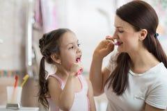 Mom teaching kid daughter teeth brushing in bathroom Stock Image