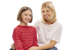 Mom and teen daughter embrace and laugh. Isolated on white background stock image