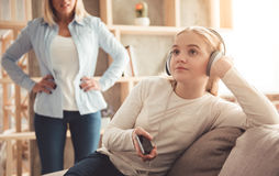 Mom and teenage daughter. Beautiful women is scolding her teenage daughter, girl is listening to music in headphones and ignoring her mom Stock Photography