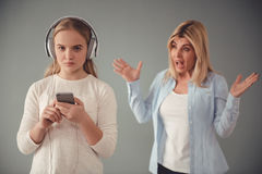 Mom and teenage daughter. Beautiful women is scolding her teenage daughter, girl is listening to music in headphones and ignoring her mom, on gray background Royalty Free Stock Photography
