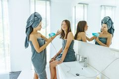Mom brushing hair to her daughter in hotel bathroom stock photo