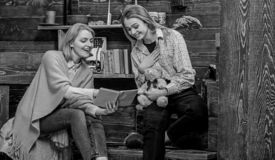 Mom and teenage girl looking through old family album. Woman and her daughter smiling while reading book, happiness and. Fun concept. Mother and kid having good stock image