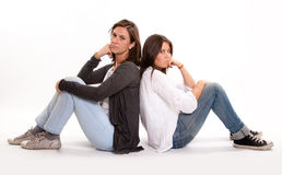 Mom and teenager anger. Isolated picture of an angry mother back to back with her teenage daughter Stock Image