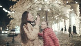 Mom and teenager daughter dance in the autumn evening along the street. Two young girls listen to music on headphones in. Two young girls listen to music on stock footage