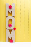 MOM text letters with carnations on yellow wooden background Royalty Free Stock Photography