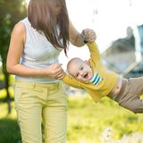 Mom throws baby in her arms up. In the park Royalty Free Stock Image