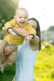 Mom throws baby in her arms up. In the park Stock Photo