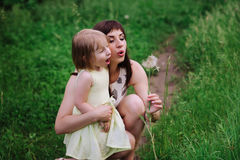 Mom throws daughter plays in sunset ligt Royalty Free Stock Image