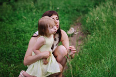 Mom throws daughter plays in sunset ligt Royalty Free Stock Photo