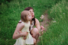 Mom throws daughter plays in sunset ligt Stock Image
