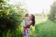 Mom throws daughter plays in sunset ligt Stock Photography