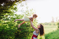Mom throws daughter plays in sunset ligt Stock Photo