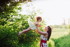 Mom throws daughter plays in sunset ligt Royalty Free Stock Photography