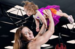 Mom throws her daughter up in the gym. royalty free stock photo