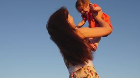 Mom throws her daughter up to the sky. mother plays with a small child against a blue sky. happy family playing in the stock video footage