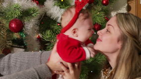 Mom throws up baby near Christmas tre stock video