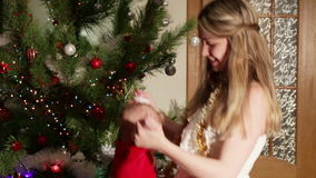 Mom throws up baby near Christmas tre stock footage
