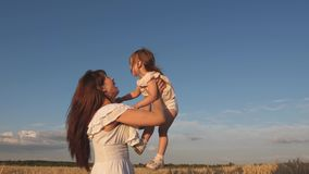 Mom throws up a happy daughter in the sky. mother and little baby play on a field of ripe wheat. happy family travels stock footage