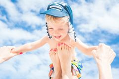 Mom throws up her kid. Happy moment,Mother throws up her smiling baby boy in the blue sky,summer time Stock Photos