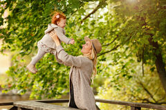 Mom throws up a red baby girl and laughing, autumn Stock Photo