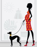 Mom-To-Be passing by a baby shop with her dog Stock Image