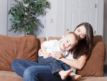 Mom and toddler fun tickle play. Young mother and her toddler son sitting on couch tickling and horseplaying to bond and have a lot of fun together Royalty Free Stock Images