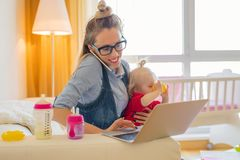 Mom with toddler working on computer. While sitting at home Royalty Free Stock Photo