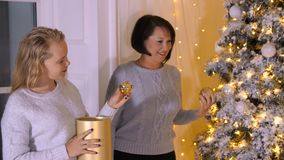 Mom together daughter decorating Christmas tree in living room at holiday eve. Mother with daughter preparing to stock video footage