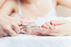 Mom tonsured nails on the hands newborn using nail scissors Royalty Free Stock Photography