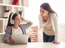 Mom and troubled daughter. Troubled teenage girl in headphones is using a digital tablet while her mom is scolding Royalty Free Stock Photo