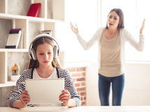 Mom and troubled daughter. Troubled teenage girl in headphones is using a digital tablet while her mom is scolding in the background Stock Images