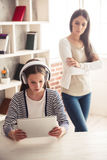 Mom and troubled daughter. Troubled teenage girl in headphones is using a digital tablet while her mom is standing with crossed arms in the background Stock Image