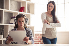 Mom and troubled daughter. Troubled teenage girl in headphones is using a digital tablet while her mom is standing with crossed arms in the background Stock Photography