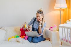 Mom trying to work while babysitting her child. Mom trying to work while babysitting at home with her child royalty free stock image