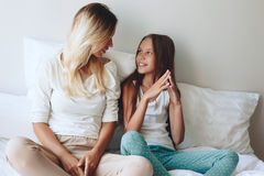 Mom with tween daughter. Mom with her tween daughter relaxing in bed, positive feelings, good relations Royalty Free Stock Photo
