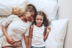 Mom with tween daughter. Mom with her tween daughter relaxing in bed, positive feelings, good relations. Top view Stock Photos