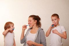 Mom and two blond boys brush their teeth Royalty Free Stock Photos