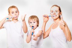 Mom and two blond boys brush their teeth Royalty Free Stock Image