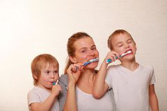 Mom and two blond boys brush their teeth Stock Photo
