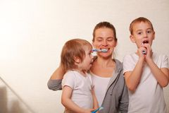 Mom and two blond boys brush their teeth Royalty Free Stock Images