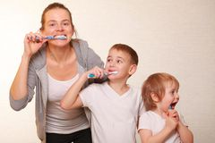 Mom and two blond boys brush their teeth. Family mom and two blond boys brush their teeth stock images