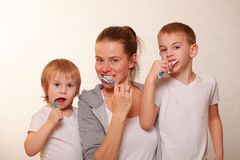 Mom and two blond boys brush their teeth. Family mom and two blond boys brush their teeth royalty free stock photo