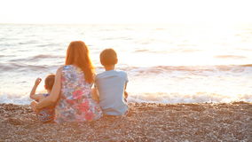 Mom with two boys sitting on a beach with sons sea at sunset. Throw stones stock footage