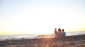 Mom with two boys, sons of rest on the beach by the sea at sunset, stock video footage
