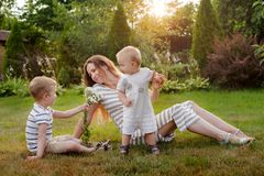 Mom, two children rest on nature. Sibling rivalry. Brothers, Motherhood. Mom, two children rest on nature. Sibling rivalry. Brothers, the son gives his mother stock photos