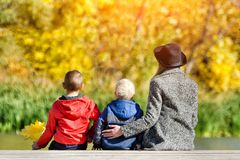 Mom and two children are sitting on the pier. Sunny autumn. Back. View Stock Images