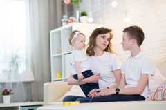 Mom with two children. Of twelve years and eleven months of age in the room stock photography