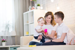 Mom with two children. Of twelve years and eleven months of age in the room stock images